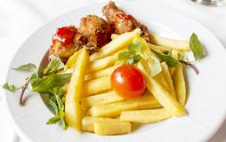 A plate of chicken on the bone in breadcrumbs, served with French fries cut into strips, decorated with tomato . To the dinner plate with chicken on the bone in stock image