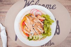 Plate with chicken salad on table. Caesar Salad. royalty free stock photo