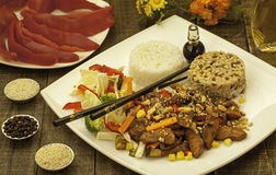 Plate with chinese food. White plate with chinese food, chopped meat, rice and red paprika Stock Image