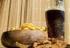 Plate of chips, glass of dark beer with foam, bubbles and crackers on wooden background Royalty Free Stock Photo