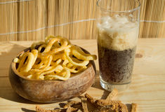 Plate of chips, glass of dark beer with foam, bubbles and crackers on wooden background Royalty Free Stock Image