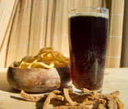 Plate of chips, glass of dark beer with foam, bubbles and crackers on wooden background Stock Image