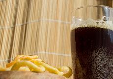 Plate of chips, a glass of dark beer with foam, bubbles on wooden background Royalty Free Stock Image