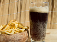 Plate of chips, a glass of dark beer with foam, bubbles on wooden background Stock Photos