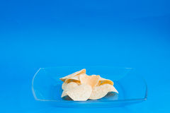 Plate of chips unhealthy food. On blue color background Stock Images