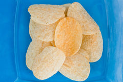 Plate of chips unhealthy food. Macro plate of chips unhealthy food on blue color background Royalty Free Stock Images