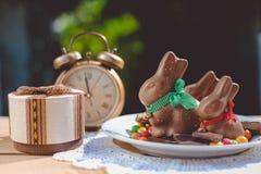 Plate with chocolate bunnies beside retro alarm Stock Image