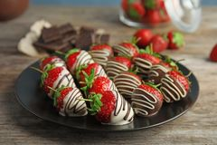 Plate with chocolate covered strawberries. On table royalty free stock photos