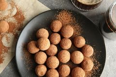 Plate with chocolate truffles on grey background. Top view stock photo