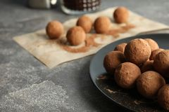 Plate with chocolate truffles on grey background. Space for text stock photo