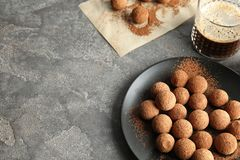 Plate with chocolate truffles on grey background. Space for text royalty free stock image