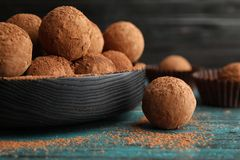 Plate of chocolate truffles on wooden table. Closeup royalty free stock images