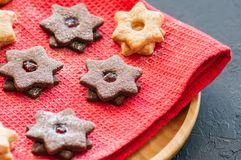 Plate of chocolate and vanilla linzer star cookies with raspberry and orange jam. Festive Christmas dessert. stock image