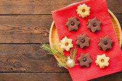 Plate of chocolate and vanilla linzer star cookies with raspberry and orange jam. Festive Christmas dessert. stock photos