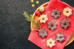 Plate of chocolate and vanilla linzer star cookies with raspberry and orange jam. Festive Christmas dessert. royalty free stock photography