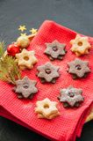 Plate of chocolate and vanilla linzer star cookies with raspberry and orange jam. Festive Christmas dessert. royalty free stock image