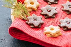 Plate of chocolate and vanilla linzer star cookies with raspberry and orange jam. Festive Christmas dessert. stock photo