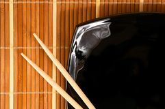 Plate with chopsticks. Japananese style plate on bamboo rug Royalty Free Stock Images