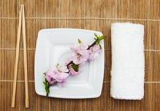 Plate, chopsticks and sakura branch Stock Photos