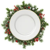 Plate in a Christmas wreath. Royalty Free Stock Photography