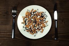 Plate with cigarettes stubs Royalty Free Stock Image