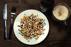 Plate with cigarettes stubs Royalty Free Stock Photos