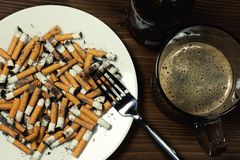 Plate with cigarettes stubs Stock Photography