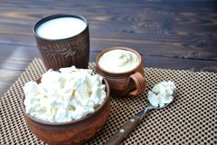 A plate of clay with cottage cheese, a mug of clay with sour cream, a mug with milk and a spoon with cottage cheese on a table royalty free stock photo