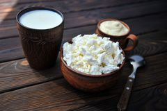 A plate of clay with cottage cheese, a mug of clay with sour cream, a mug with milk and a spoon on a tablen royalty free stock images