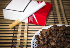 Plate with coffee beans in front of a cigarette Royalty Free Stock Photos