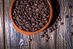 A plate of coffee beans on a wooden background Stock Images