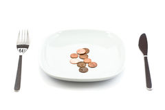 Plate with coins. Plate with silverware and coins isolated on white background royalty free stock photos