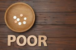 Plate with coins, word POOR and space for text on wooden background. Top view stock image