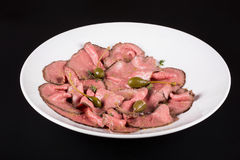 Plate of cold cuts with capers.Cutting meat on a plate with capers.  Stock Images