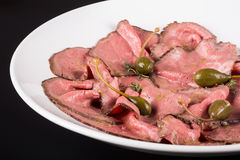 Plate of cold cuts with capers.Cutting meat on a plate with capers. Close up.  Stock Photos