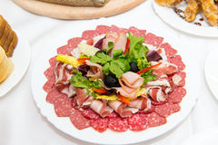 Plate of cold meats in the restaurant. Meat snacks. Smoked sausage and bacon, Stock Image