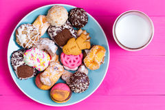 Plate of colorful cookies with a serving of milk Royalty Free Stock Photography