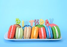 Plate of colorful macaron cookies for birthday on blue. Many colorful macaron cookies on a white rectangular plate, birthday candles spelling the word BIRTHDAY stock photo