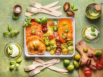 Plate with colorful sliced tomatoes for tasty eating. Mediterranean ingredients on kitchen table. Top view royalty free stock photos