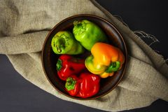 Plate with colorful sweet peppers on a linen napkin background in rustic style. Plate with red, green and yellowl sweet peppers on a linen napkin background in Royalty Free Stock Photos