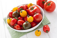Plate with colorful tomatoes. On a white wooden board Stock Image