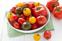 Plate with colorful tomatoes. On a white wooden board Stock Photo
