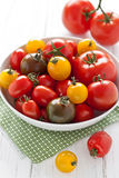 Plate with colorful tomatoes. On a white wooden board Stock Photos