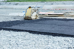 Plate compactor. Vibratory plate compactor compacting asphalt at road repair Royalty Free Stock Photography