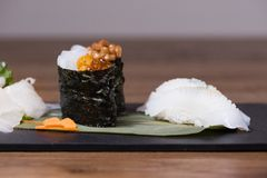 Plate composed of squid and cuttlefish sashimi, caviar and fermented soy gunkan, grilled squid nigiri. Garnished with daikon salad and carrots royalty free stock image