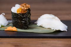 Plate composed of squid and cuttlefish sashimi, caviar and fermented soy gunkan, grilled squid nigiri. Garnished with daikon salad and carrots royalty free stock photo
