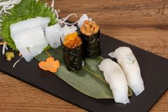 Plate composed of squid and cuttlefish sashimi, caviar and fermented soy gunkan, grilled squid nigiri. Garnished with daikon salad and carrots stock photos