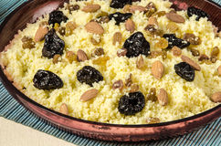 Plate with cooked couscous with almond, raisins and prunes Royalty Free Stock Photos