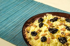Plate with cooked couscous with almond, raisins and prunes Royalty Free Stock Photography