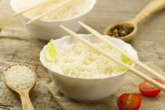 Plate of cooked long-grain rice on wooden background. Healthy eating, diet, vegetarianism. Royalty Free Stock Images
